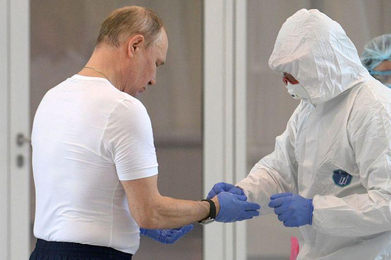 普亭(左)24日造訪收治新冠肺炎患者的醫院,換穿防護裝備。法新社