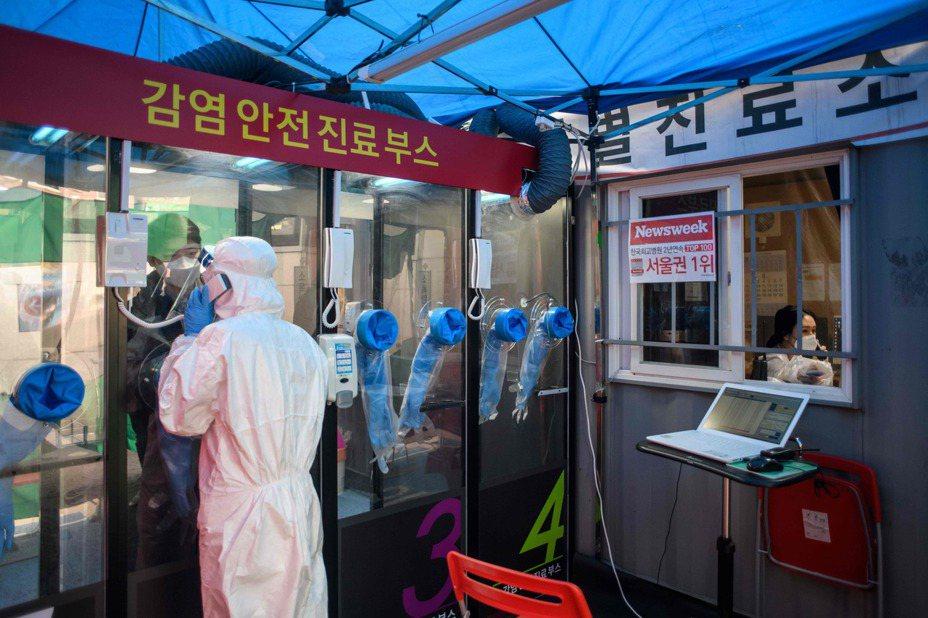 首爾陽智醫院外設置新冠肺炎採檢站,醫護人員和民眾隔著透明牆完成採檢,降低接觸的感染風險。 法新社