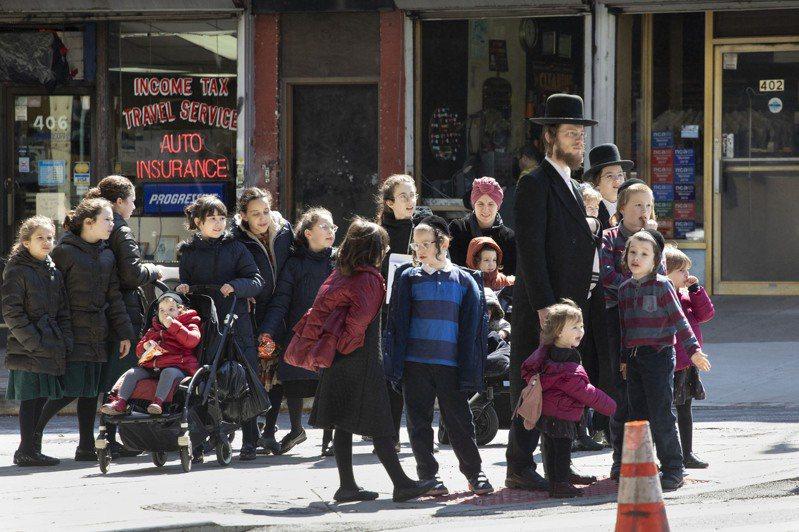 有些州的民眾不遵守規定,仍然繼續到處行動。圖為紐約民眾24日仍在街上聚集。(美聯社)
