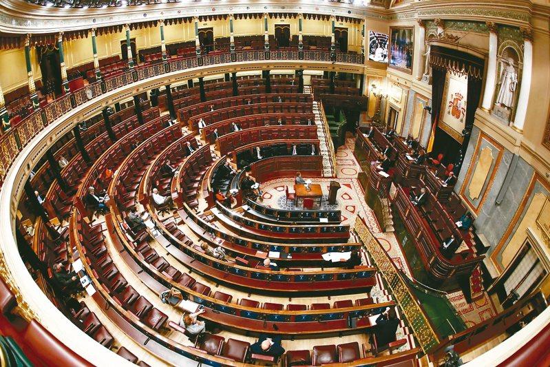 西班牙死亡案例已超過中國大陸,圖為西國總理桑契斯在幾乎唱空城的國會進行報告,大部分議員靠視訊參與。 美聯社