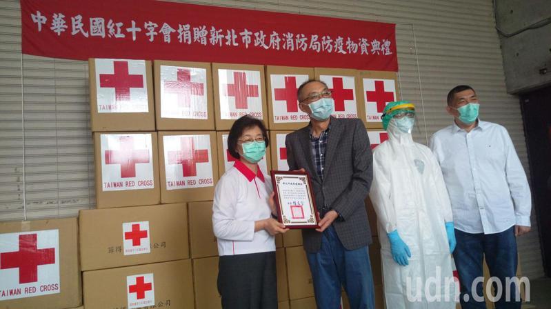 中華民國紅十字會總會長王清峰(左)今天捐防疫物資,協助新北消防局第一線救護人員對抗新冠肺炎,由新北市副市長謝政達(左二)代表受贈並回贈感謝狀。記者王長鼎/攝影