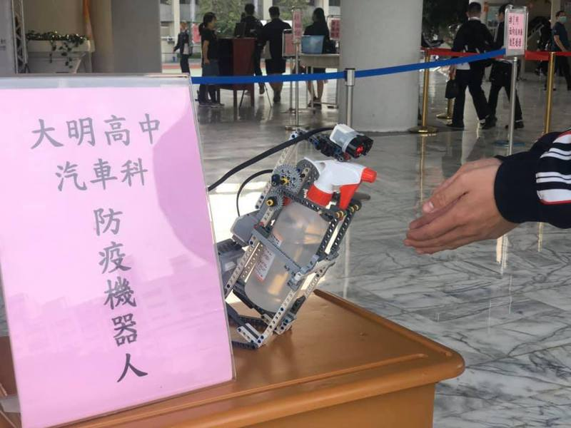 台中市大明高中汽車科二年級學生游冠傑設計了一款「防疫機器人」取代人工噴霧,終於讓負責噴霧的師長和志工同學不再手抽筋。圖/大明高中提供
