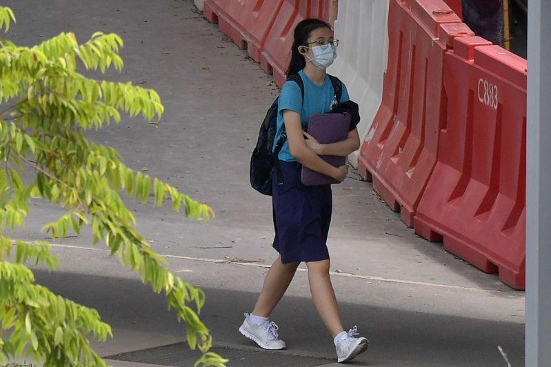 新加坡學生戴口罩步行上學。法新社