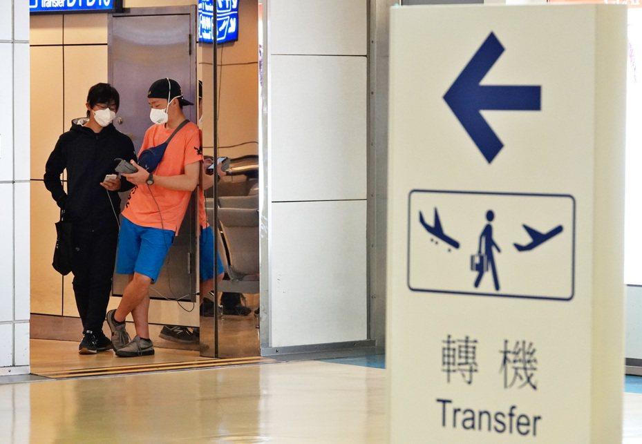 因為紐西蘭航空搞烏龍,載了三名非紐西蘭裔的外籍旅客入境桃園機場轉機,結果因為台灣轉機禁令及紐西蘭禁外人入境,三人無法轉機,也無法原機回紐西蘭,目前只能受困桃園機場管制區內,兩名日籍旅客靠在牆邊讓手機充電。記者鄭超文/攝影