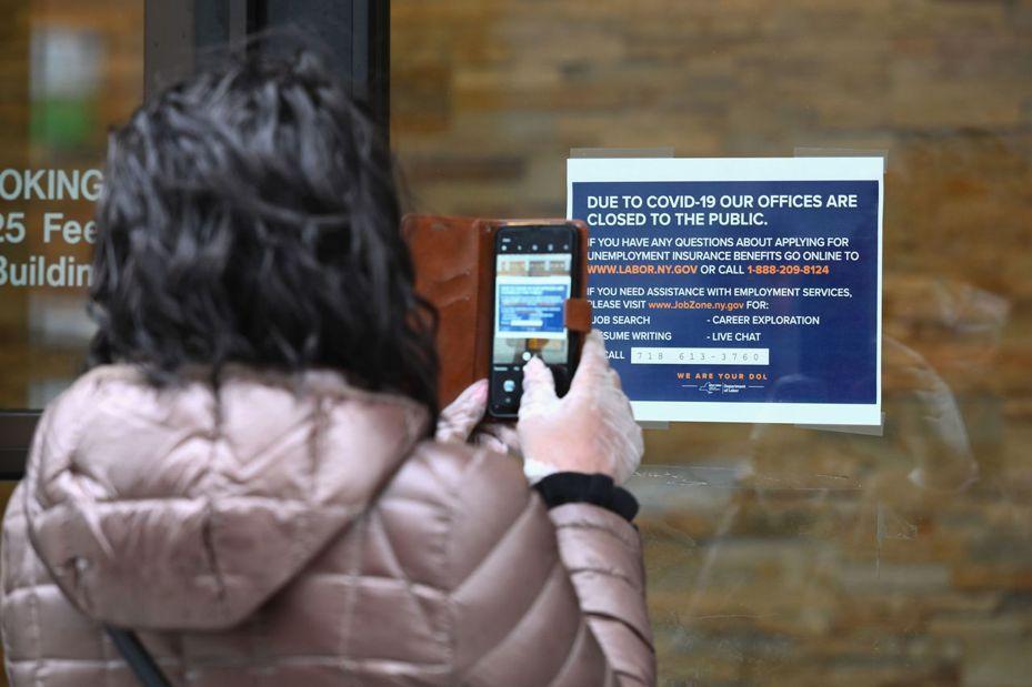 美國一名女子在關閉的勞工部外拍下申請失業救濟金相關資訊。法新社