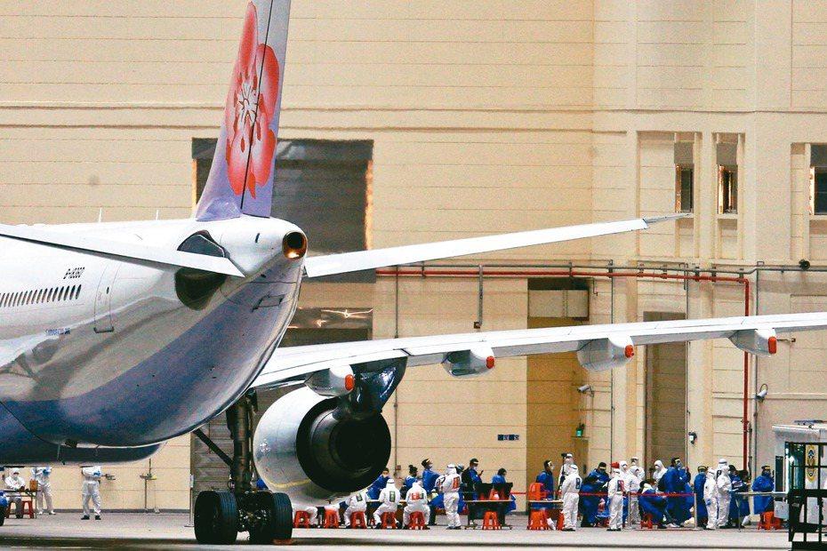第二批武漢返台專機三月十日抵達桃園機場後,乘客身著隔離服排隊準備檢疫。 圖/聯合報系資料照片