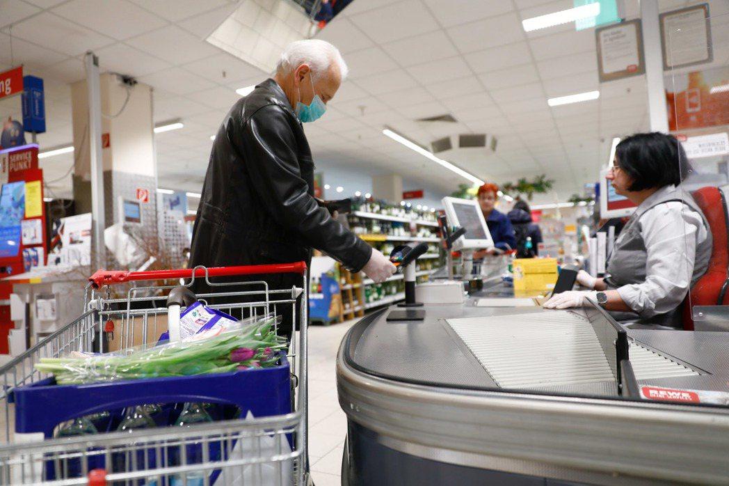 民眾在超市結帳。3月20日攝於德國。 圖/路透社