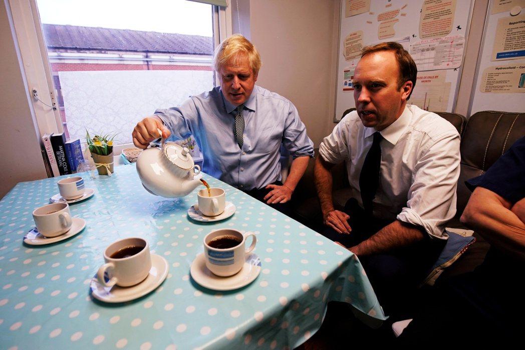 一起喝茶一起染病。圖左為首相強生,右為同日確診的衛生大臣韓考克。 圖/路透社