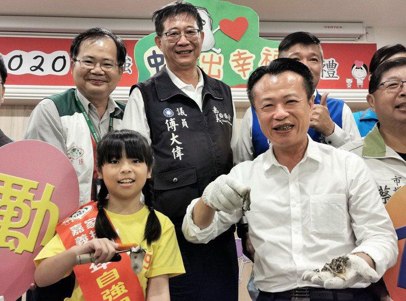 小學三年級的蔡芷辰(前排左),今天指導嘉義縣長翁章梁剖蚵。記者卜敏正/攝影