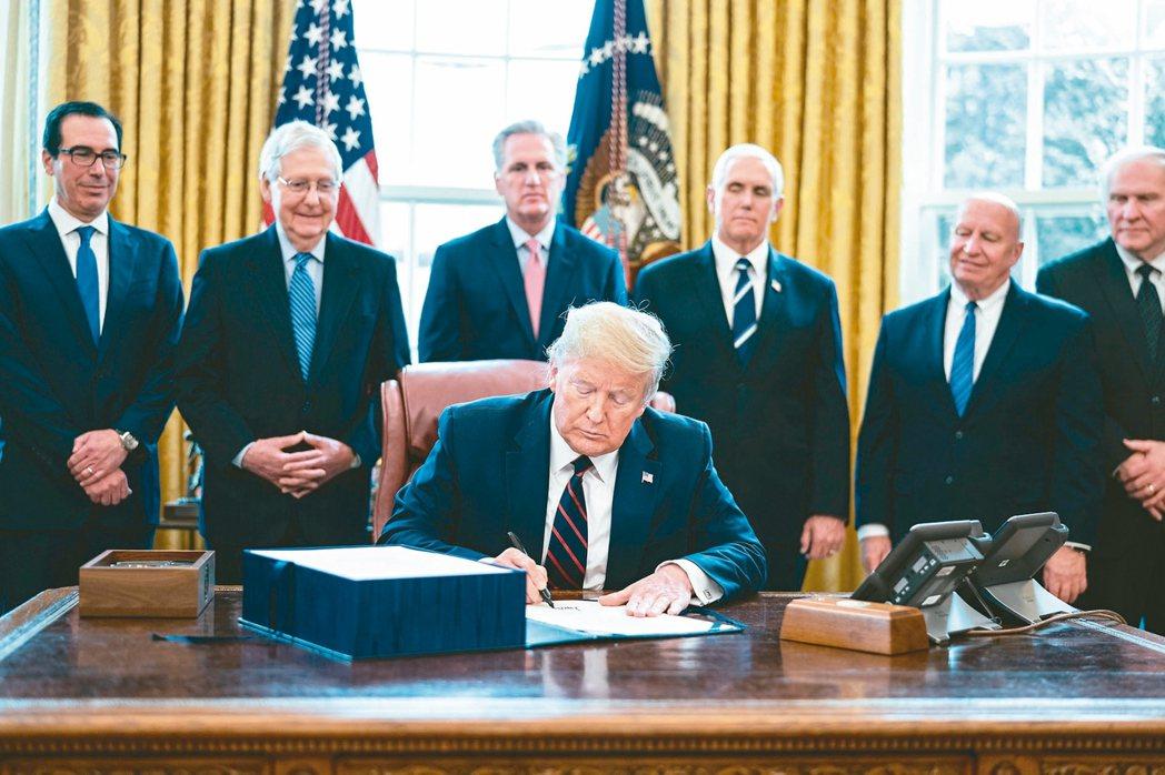 美國總統川普(前)27日簽署2.2兆美元的的振興經濟方案。 美聯社