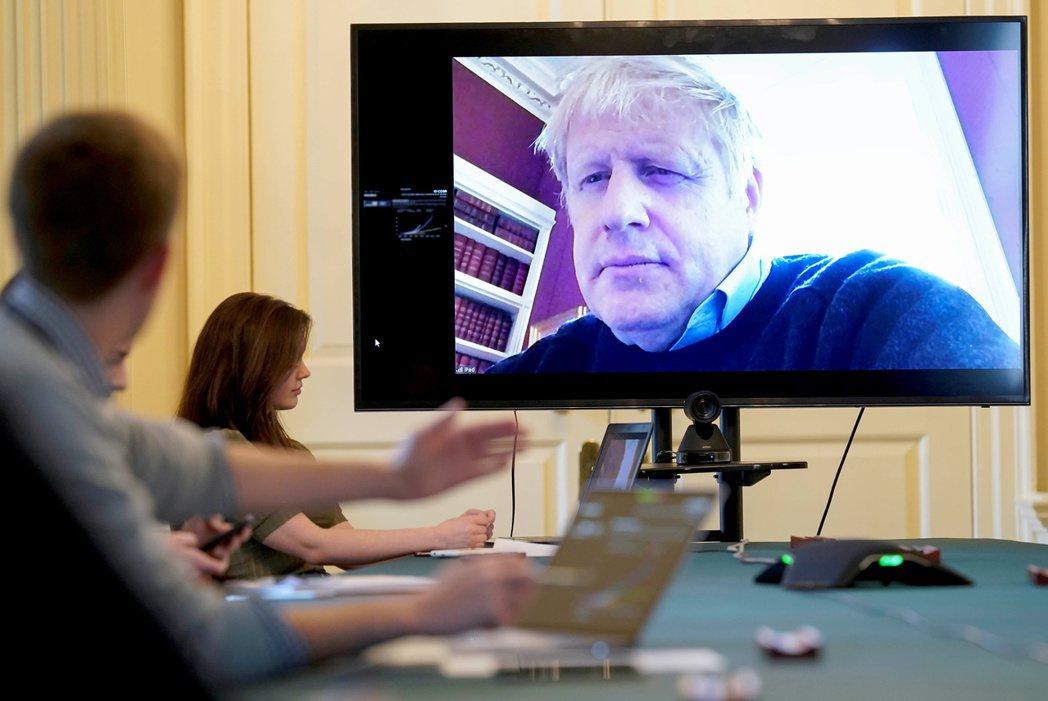 正在自我隔離的英國首相強生28日透過視訊參加新冠病毒疫情會議。 (路透)