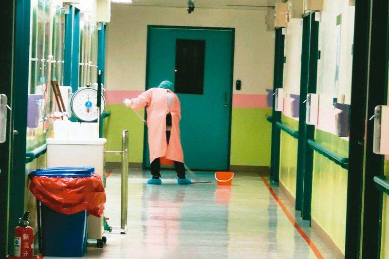 武漢包機返台旅客赴醫院採檢的當晚,清潔員孤獨清掃旅客走過的每個角落。 圖/陳中岳提供