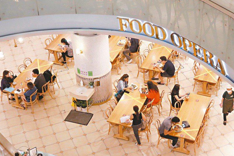 新加坡一間美食廣場廿五日將用餐區部分桌椅用膠帶標示,鼓勵民眾保持社交距離防止新冠肺炎傳播。(路透)