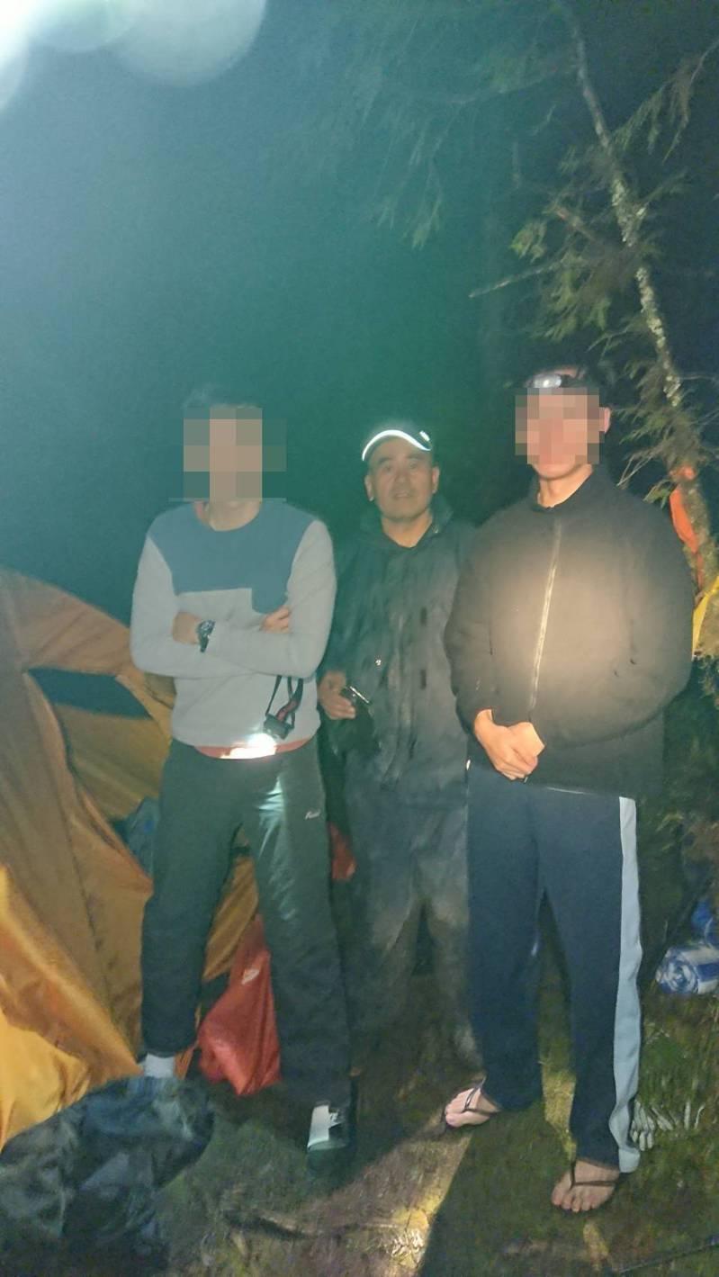 太平山派出所所長柯榮雄(中)入夜帶隊上山搜救,找到兩名迷航的年輕登山客,昨天下午把他們送下山。圖/太平所提供
