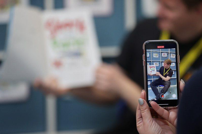 臉書視訊及即時傳訊流量近來爆增。圖為英國一家托兒所拍攝影音貼到自家app及FB,提供居家避疫的幼兒使用。路透