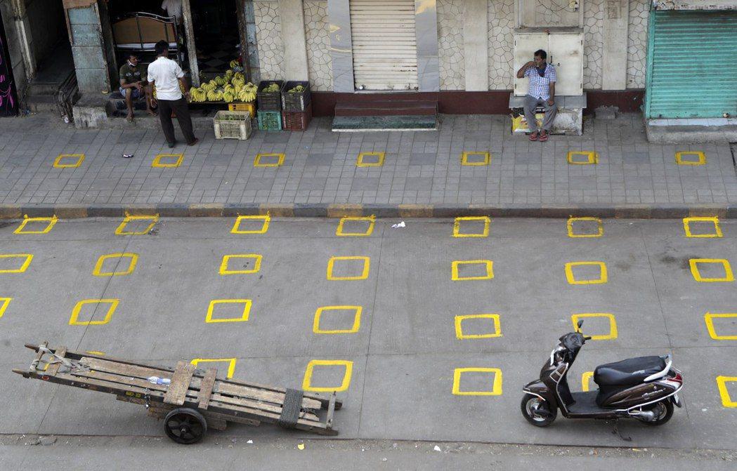 孟買一處市場外的地面上劃有格子,讓排隊的顧客知道要保持什麼樣的距離,以策安全。 ...