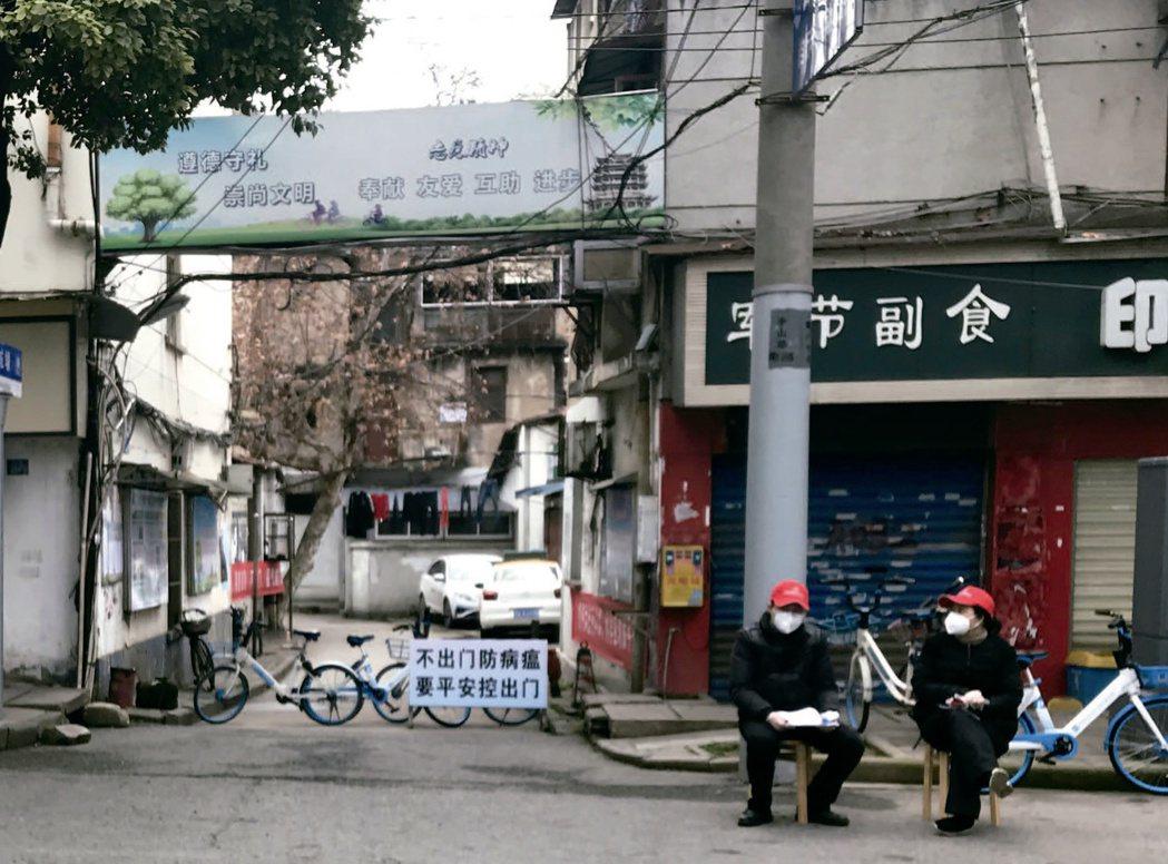 一處被封閉的小區,路口有一個工作站。圖/聯經出版 提供