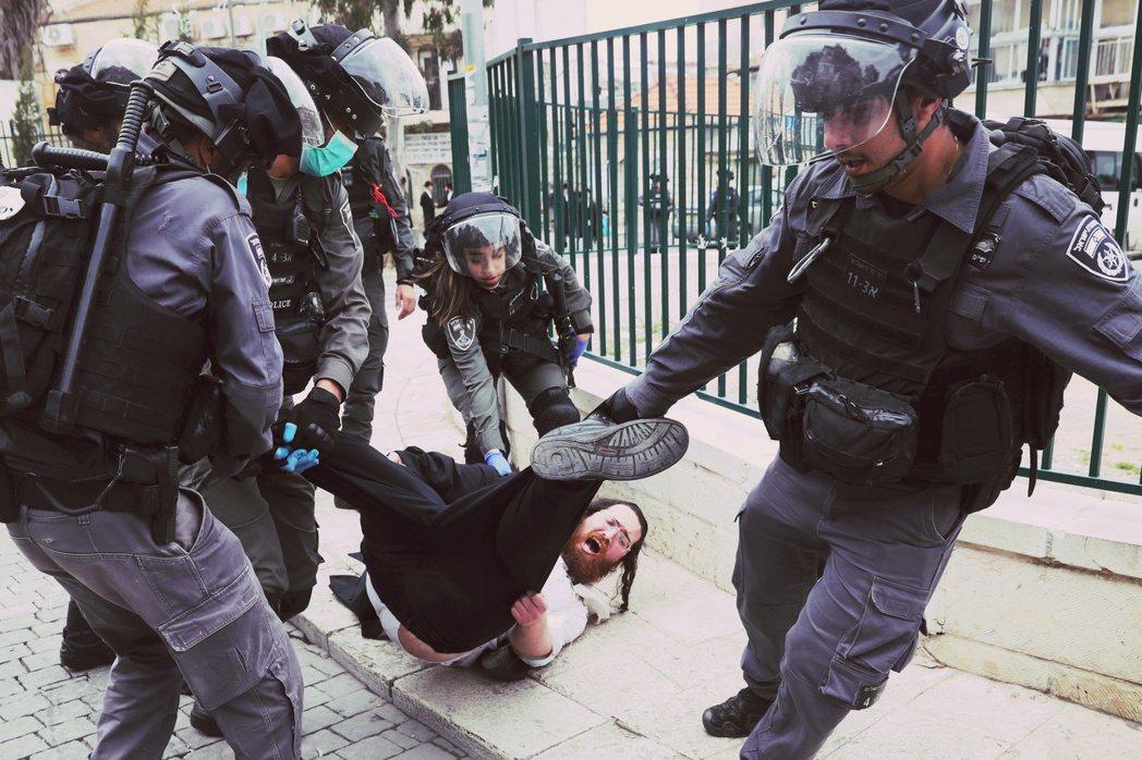 圖為30日,警察逮捕在百倍之地街上示威的哈雷迪信徒。 圖/法新社