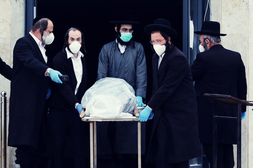 圖為26日,哈雷迪信徒從耶路撒冷的殯儀館中,推出染病死者的屍體。 圖/歐新社