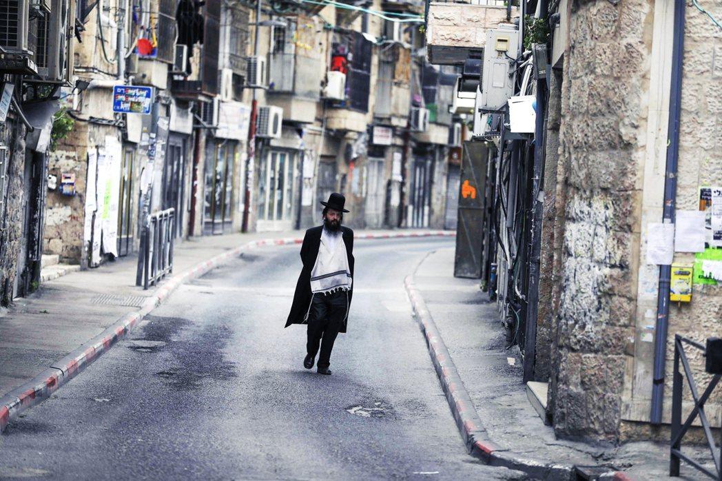 31日,一名哈雷迪信徒走在耶路撒冷空盪的街上。 圖/法新社