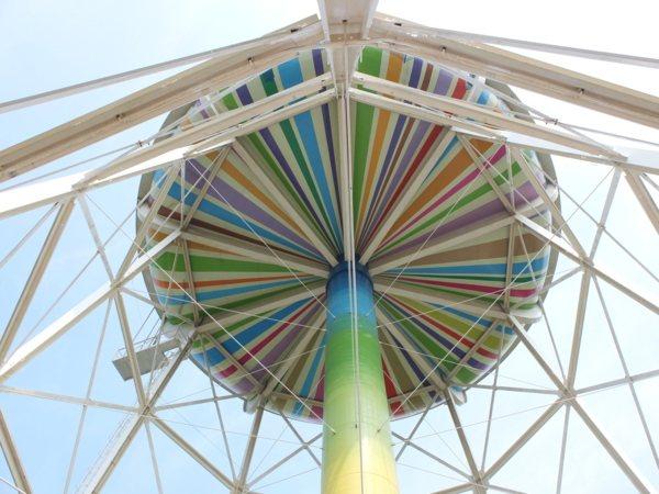 ▲如彩虹般鮮豔亮麗的線條色將水塔裝扮成像一份大禮物,換個角度看,也有人形容是一台彩色的外星飛碟,還真有趣。