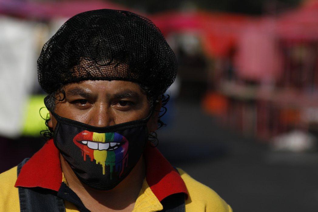 在墨西哥市北邉一處市場工作的男子29日戴著口罩和網帽上工,市場生意因為新冠疫情顧...