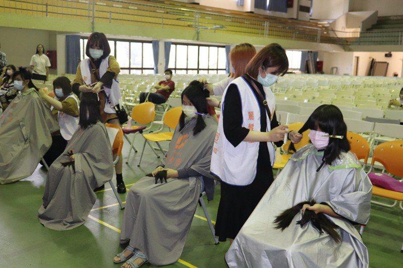 台南女中「牽君一髮」活動,學生、教職員、社區居民捐髮助癌症患者。圖/台南女中提供
