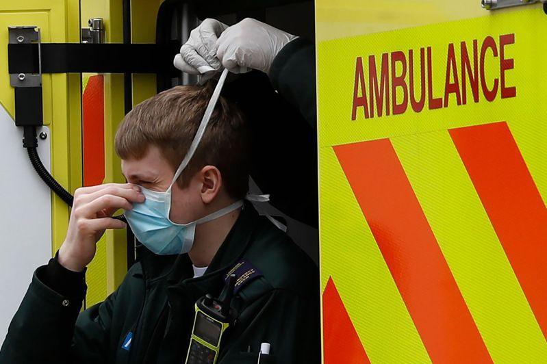 英國醫護人員出動前,由同事幫忙帶口罩。法新社