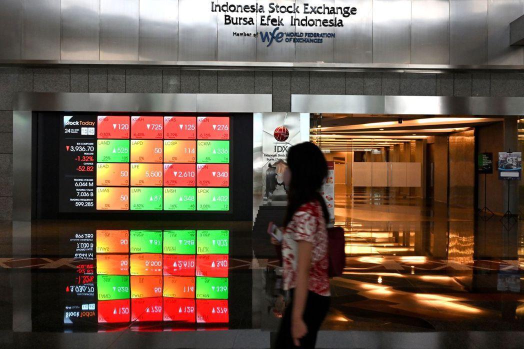 圖為印尼證交所內一處顯示股市行情的螢幕牆。法新社