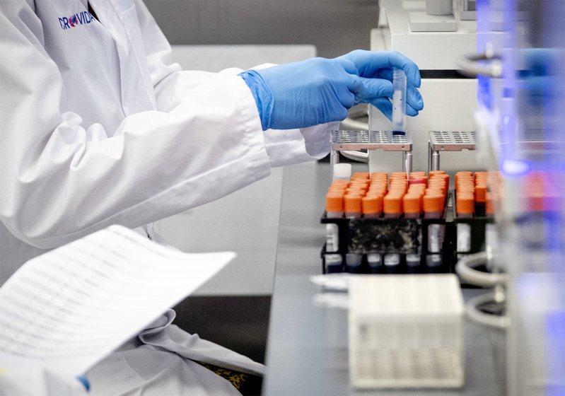 圖為醫事人員對新冠病毒進行檢測。歐新社
