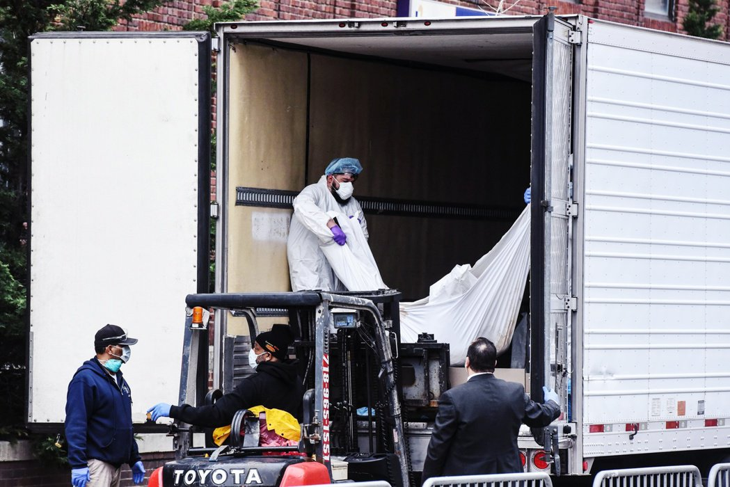 紐約布魯克林醫院31日把超量死者移至冷凍車上綻放安置。 圖/法新社