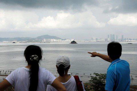 一名遊客在金門烈嶼指向中國廈門。 圖/路透社