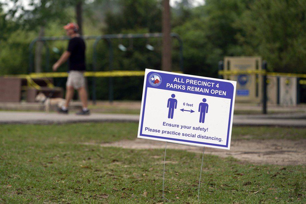 美國休士頓一處公園放置提醒民眾保持社交距離的標誌。 圖/美聯社