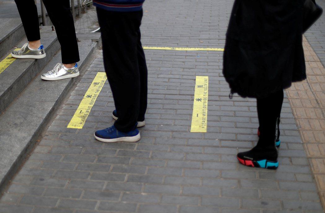 北京一處超市在地上標示「一米線」,確保排隊民眾距離。 圖/路透社