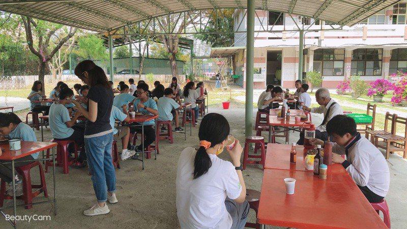 台南市官田國小兒童節招待小朋友吃牛排大餐,為了防疫改到戶外,還依照「防疫距離」位置錯開。圖/校方提供