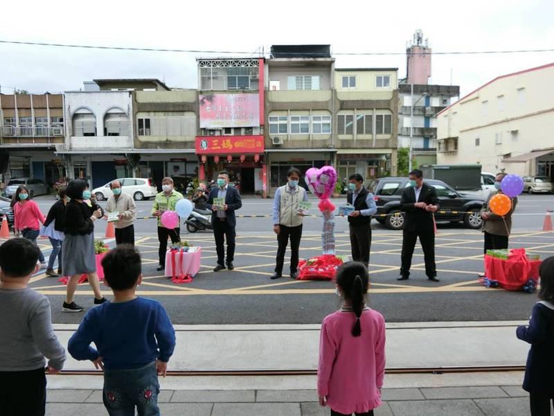 冬山鄉公所贈送兒童節禮物,鄉長與代表們站在校門口,保持遠遠的社交距離祝賀兒童節,還是第一次見到。圖/鄉公所提供