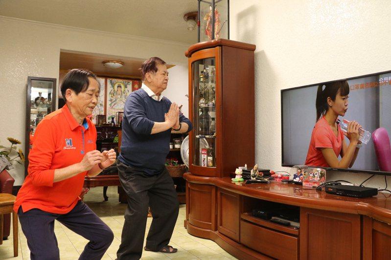家住永和的劉國年(右起)和鄭美知子,一起看電視教學跟著運動。圖/新北社會局提供
