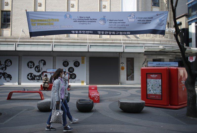 首爾街頭懸掛提醒民眾注意防疫的布條。美聯社