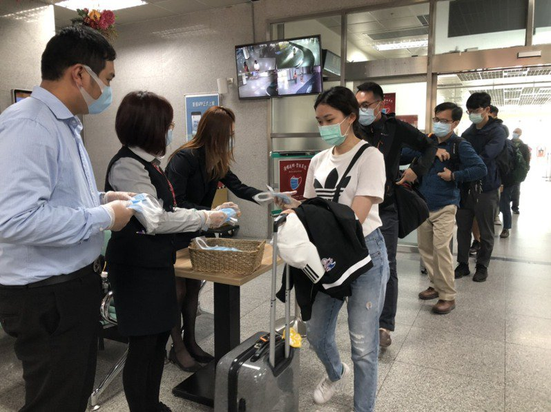 聖祖食品公司今天在尚義機場的入境處發送口罩,民眾都自動自發的排隊領取。記者蔡家蓁/攝影