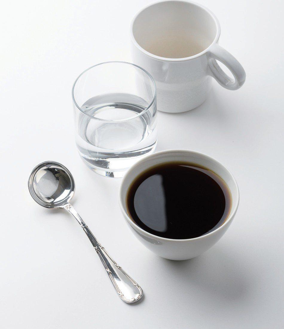 準備巴哈咖啡館杯測用的物品:裝著現煮咖啡的杯子、杯測杓、裝著洗湯匙用水的玻璃杯、...