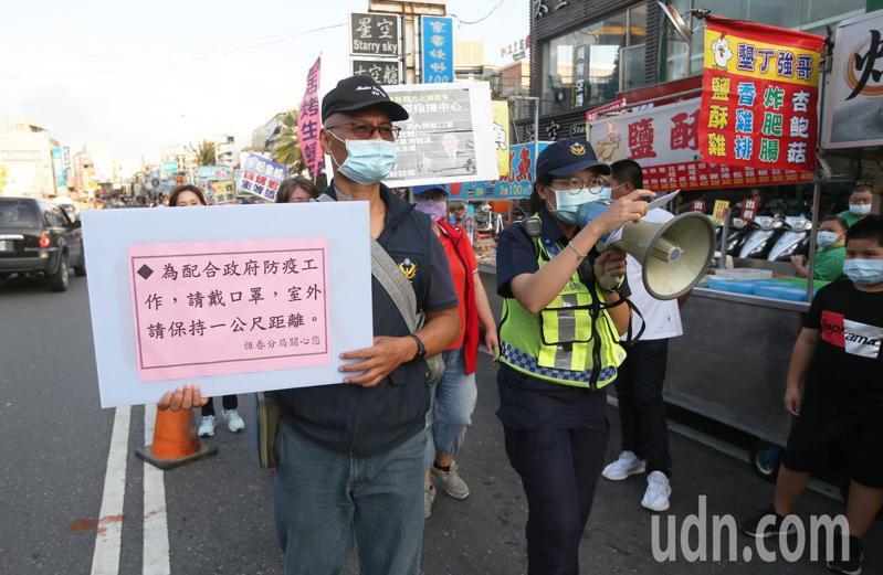 警方會同衛生局人員在墾丁大街上宣導民眾要保持社交距離。記者劉學聖/攝影