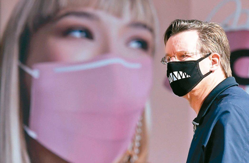 烏克蘭烏克蘭基輔街頭戴口罩的路人,經過廣告看板前。 法新社