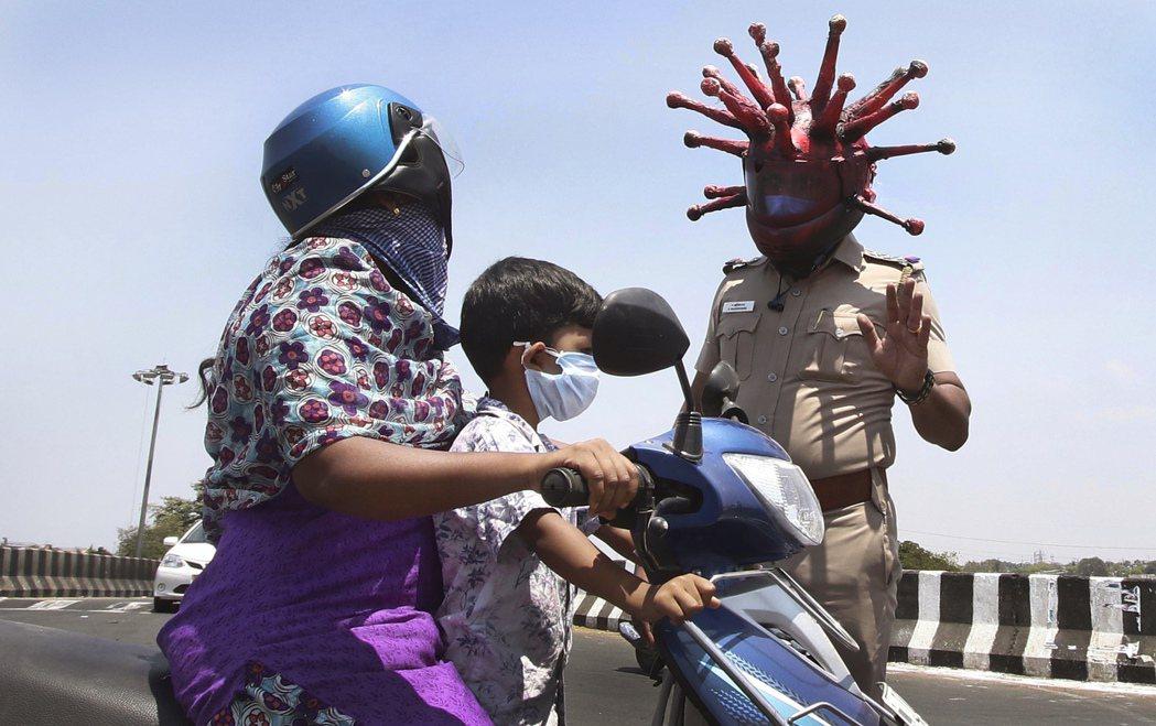 印度為防堵新冠肺炎疫情,宣布3月25日起全國禁足21天。戴著新冠病毒形狀安全帽的...