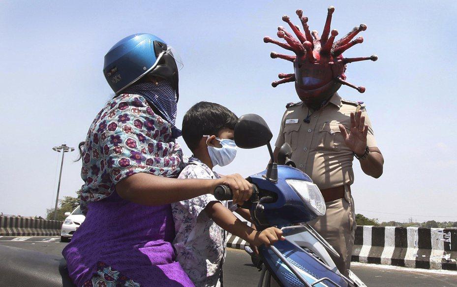 印度為防堵新冠肺炎疫情,宣布3月25日起全國禁足21天。戴著新冠病毒形狀安全帽的警官巴布在清奈要求外出民眾返家避疫。(圖/美聯社)