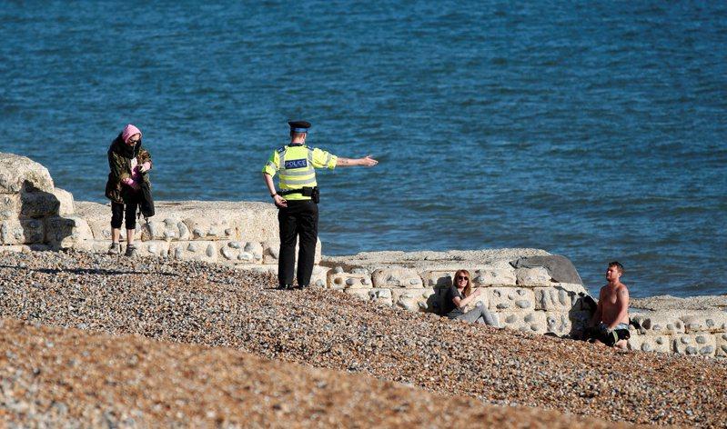一名英國警察4日勸離在布萊頓(Brighton)海灘上做日光浴的民眾。路透
