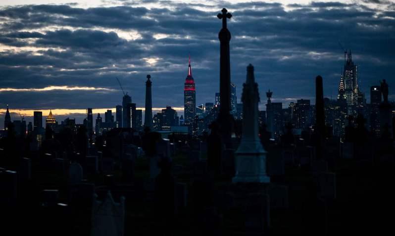 紐約州疫情全美最嚴重,過去24小時新增594起死亡病例。圖為從紐約市一處公墓望去的大蘋果天際線。法新社
