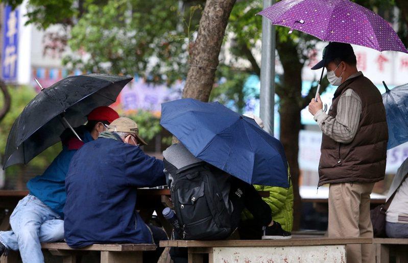 細雨綿綿的清明連假收假日,澆不熄公園裡長者對弈興致,棋友聚集,戴口罩、撐傘下棋解悶。記者侯永全/攝影