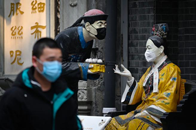 北京是中共領導人居住的地方,不容有失。圖為一家飯店門口塑像也戴起了口罩。(法新社...