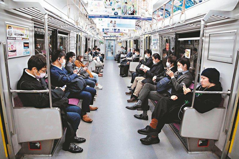 因應新冠肺炎疫情擴大,日本首相安倍晉三最快七日宣布東京、大阪等七個都府縣進入緊急狀態。圖為東京地鐵乘客六日大多戴上口罩。 (法新社)