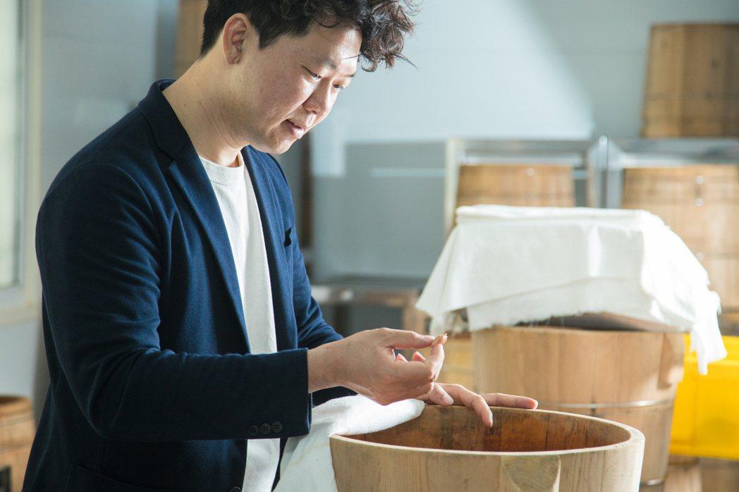 許華仁掀起耗氧發酵桶的白布,紀錄可可豆細微變化。 圖/陳立凱 攝影